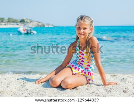 Cute happy girl sitting on the sand beach - stock photo