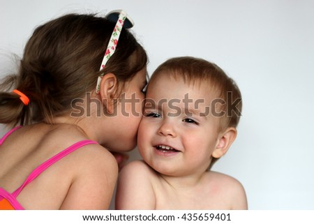 Cute happy girl wearing swimming suit and sun glasses whisper to her small brother over white background, focus on the girl, summer vacation concept - stock photo