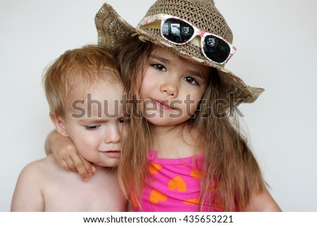 Cute happy girl wearing swimming suit and sun glasses with her small brother over white background, focus on the girl, summer vacation concept - stock photo