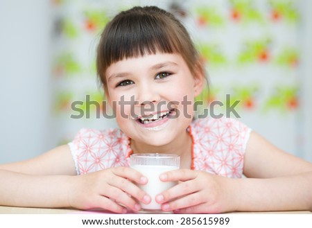 Cute happy girl with a glass of milk - stock photo