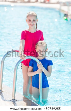 Cute happy girls at the pool in amusement aqua park. Summertime, vacation concept.