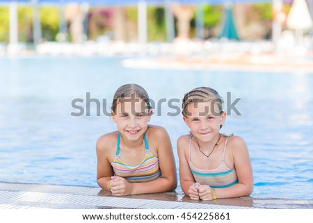 Cute happy girls at the pool in amusment aquapark. Summertime, vacation concept.