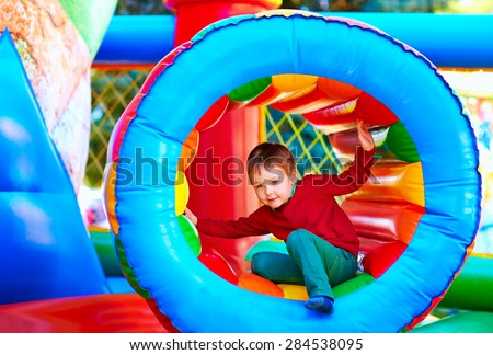 cute happy kid, boy playing in inflatable attraction on playground - stock photo