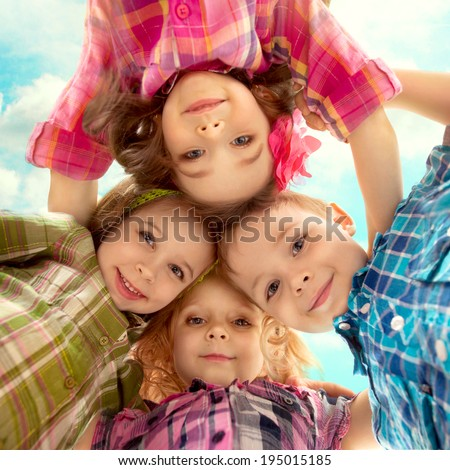 Cute happy kids looking down and holding hands. Happiness, fashionable, friendship concept - stock photo