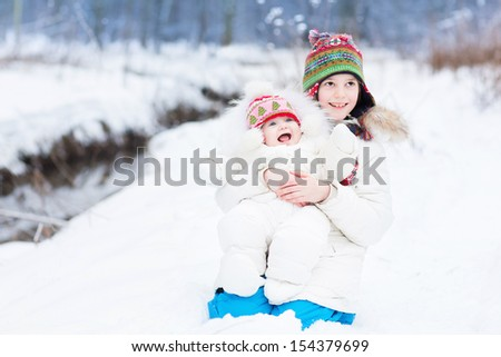 Cute happy laughing brother and baby sister playing in snow next to a river on a nice snowy cold winter day in a park - stock photo
