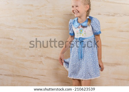 Cute happy laughing little girl giggling as she holds onto the skirt of her pretty blue summer dress, with copyspace - stock photo
