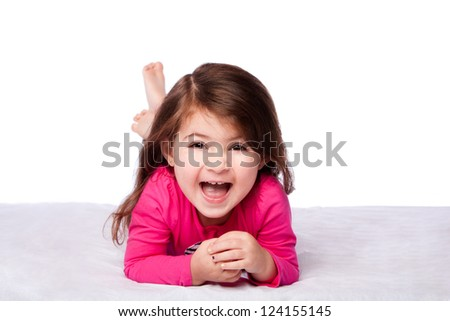 Cute happy laughing toddler child girl laying on belly supporting on elbows, on white.