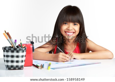Cute happy little asian girl drawing with pencils, Isolated over white - stock photo