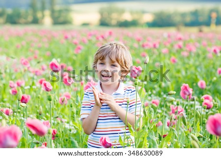 Cute happy little blond child in blooming poppy field with pink flowers. Smiling boy. Active leisure with kids in summer, on sunny warm day, outdoors.
