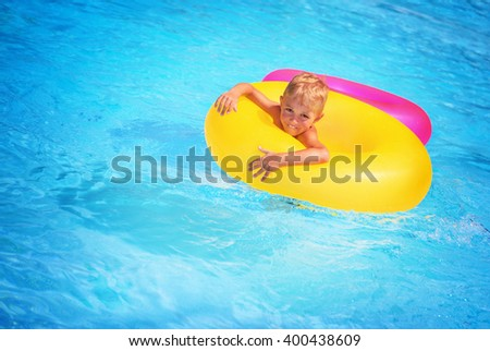 Cute happy little boy having fun in swimming pool, floating in blue refreshing water with big green rubber ring, active summer vacation on the beach - stock photo