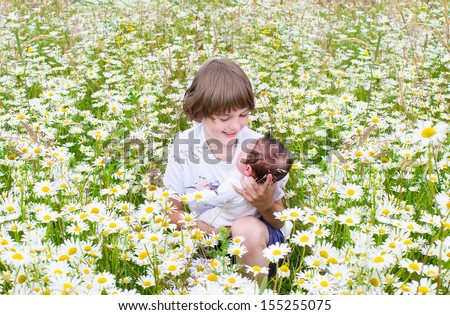Cute happy little boy holding his newborn baby sister in a beautiful daisy field - stock photo