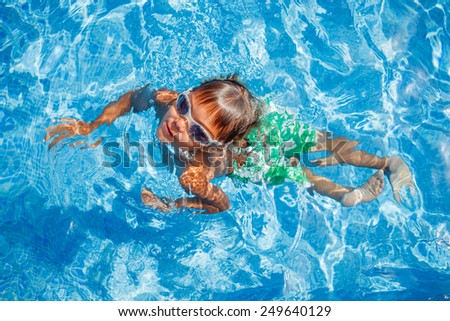 Cute happy little boy in goggles swimming and snorking in the swimming pool - stock photo