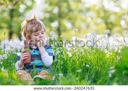 Cute happy little boy wearing Easter bunny ears at spring green grass and blooming apple garden, eating chocolate bunny and having fun outdoors.