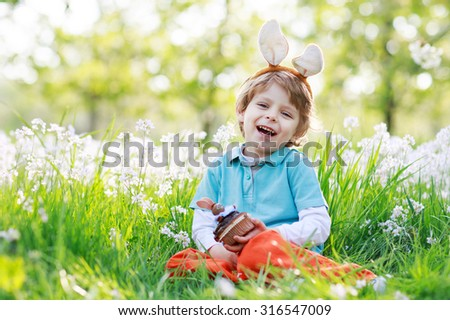 Cute happy little boy wearing Easter bunny ears at spring green grass and blooming apple garden, eating chocolate muffing with bunny and having fun outdoors.