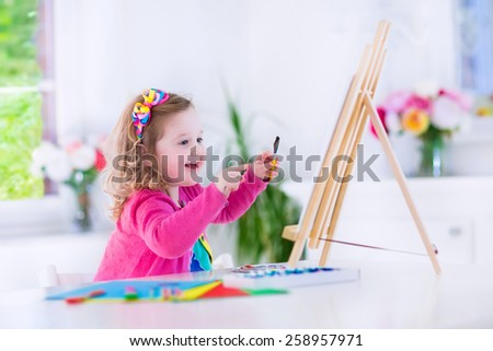 Cute happy little girl, adorable preschooler, painting with water color on canvas standing on a wooden easel in a sunny white room at home or elementary school, creative young artist at work - stock photo