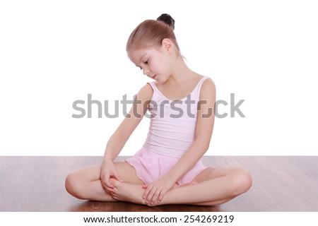 Cute happy little girl doing gymnastic exercises on the floor - stock photo