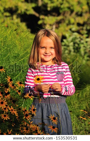cute happy little girl holding a yellow flower in the park - stock photo