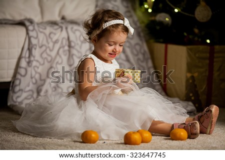 Cute happy little girl in beautiful white dress sitting on the carpet next to the christmas tree. Christmas tree with lights and gift boxes on the background. She is smiling and opening a gift box - stock photo