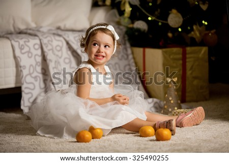 Cute happy little girl in beautiful white dress sitting on the carpet next to the christmas tree. Christmas tree with lights and gift boxes on the background. She is smiling  - stock photo
