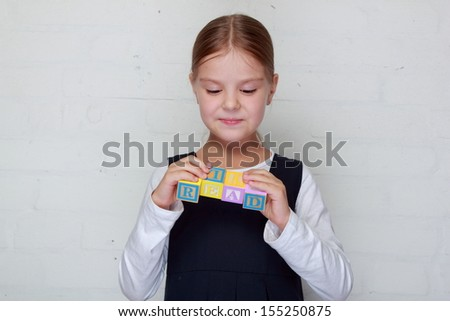 Cute happy little girl in school uniform plays with children's cubes with letters/Young schoolgirl puts the words of children's blocks on gray background - stock photo