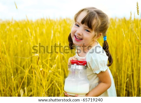 cute happy little girl in the wheat field  holding a jug with milk - stock photo