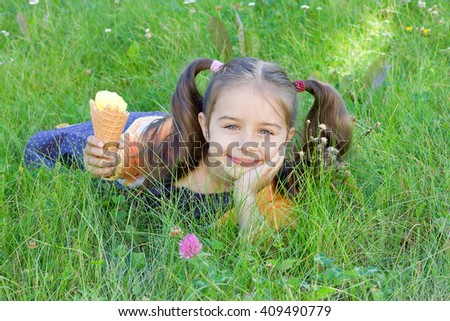 Cute happy little girl lying on the grass with ice cream in her hand  - stock photo