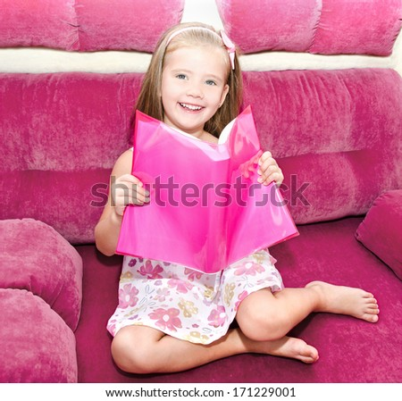 Cute happy little girl reading a book and siting on the sofa  - stock photo