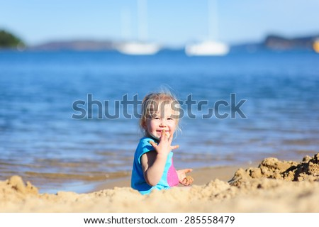 Cute happy little toddler girl playing with the sand at the beach on a sunny summer day - stock photo