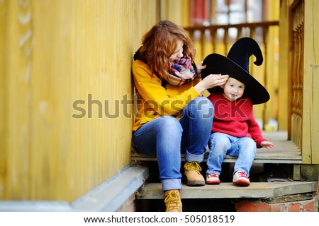 Cute happy little wizard and his young mother outdoors