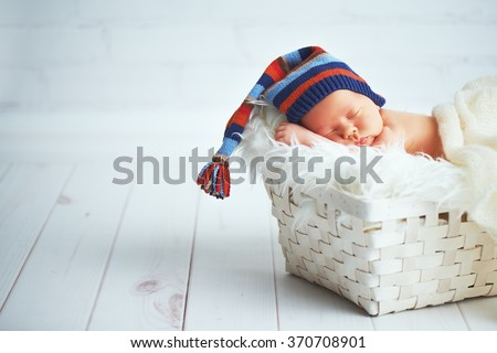 Cute happy newborn baby in a blue knit cap sleeping in a basket - stock photo