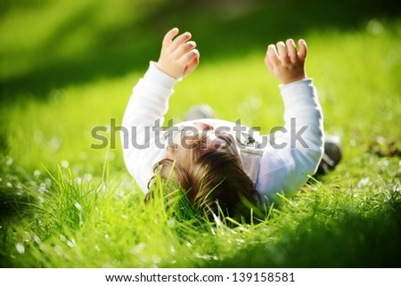 Cute happy playful baby lying alone outdoors in summer park with hands up - stock photo