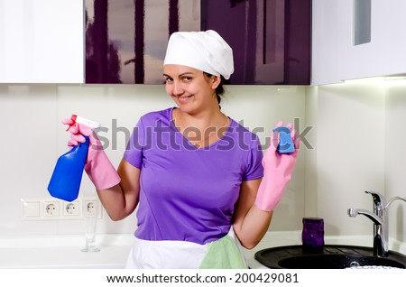 Cute happy playful housewife wearing a white cap over her long hair holding up a spray bottle and sponge as she grins at the camera - stock photo