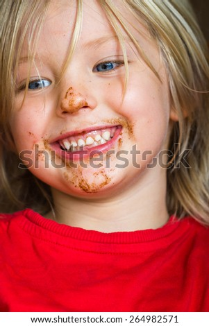 Cute, happy, smiling child with chocolate over face - stock photo