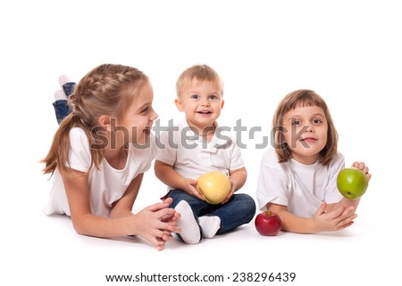 Cute happy smiling family of two sisters with junior brother posing with fruit apples - stock photo