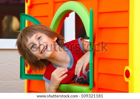 Cute happy smiling  little boy playing in toy house on playground, summer park outdoor - stock photo
