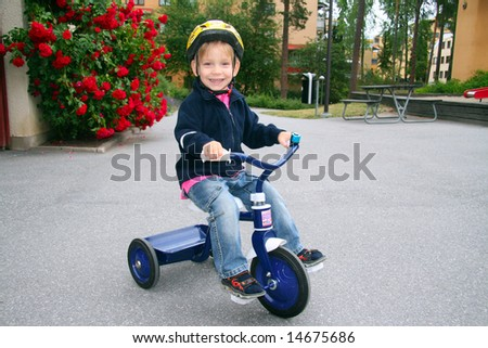 Cute happy toddler wearing helmet riding tricycle - stock photo
