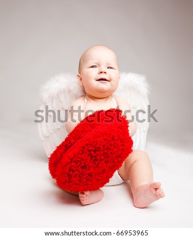 Cute happy valentine angel playing with fluffy heart, over gray - stock photo