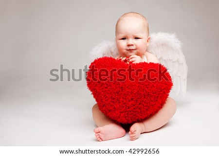 Cute happy valentine angel with red soft heart, over gray - stock photo