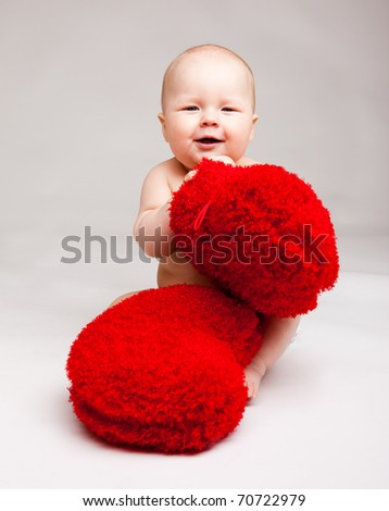 Cute happy valentine baby playing with red heart shaped pillows - stock photo