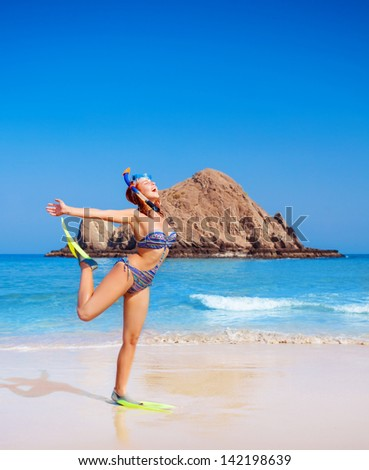 Cute happy woman wearing goggles and flippers, having fun on the beach, raised up hands, diving equipment, exotic summer vacation, snorkeling concept - stock photo