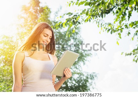 Cute happy young Caucasian brunette teenage woman with tablet computer in park on sunny summer day.  - stock photo