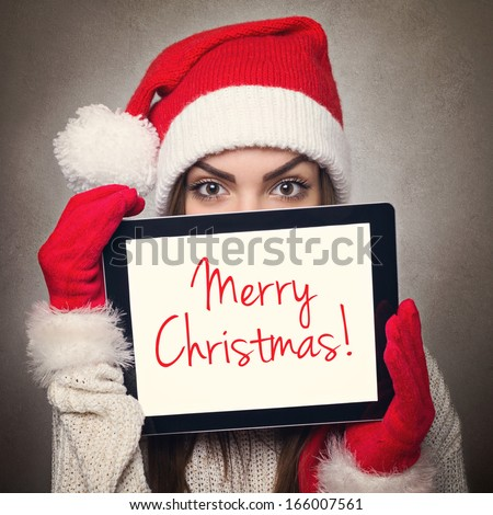 Cute happy young Caucasian woman with Santa hat hiding behind tablet computer with Merry Christmas text message. Christmas and New Year concept. - stock photo