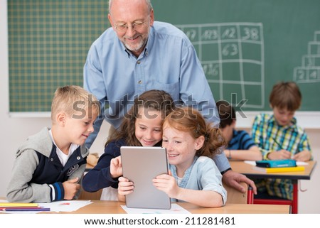 Cute happy young children in class at school smiling happily as they read something on a tablet computer under the watchful eye of a male teacher - stock photo
