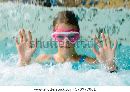 Cute happy young girl child playing in swimming pool under  a cascade of water - wearing pink goggles mask (blurred head behind waterfall, hands are sharp) - stock photo