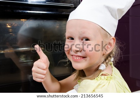 Cute happy young girl in a toque giving a thumbs up gesture of success as she crouches down alongside the oven watching a pizza bake that she has just prepared herself - stock photo