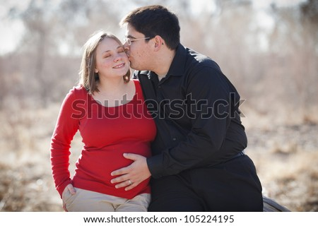 Cute happy young pregnant married couple outdoors leaning against a log.