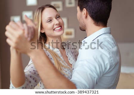 Cute happy young woman enjoying a dance in the arms of her husband as they celebrate a special occasion at home, close up head and shoulders view - stock photo