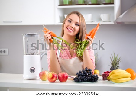 Cute healthy girl with fruits and vegetables in kitchen - stock photo