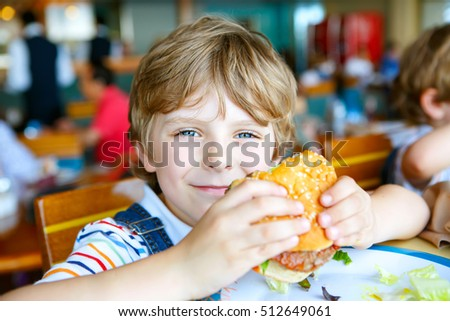 Cute healthy preschool kid boy eats hamburger sitting in cafe outdoors. Happy child eating unhealthy food in restaurant.