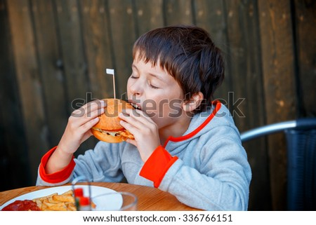 Cute healthy teenager boy eats hamburger sitting in cafe outdoors - stock photo